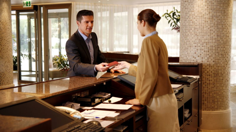 Man checking in at hotel reception desk
